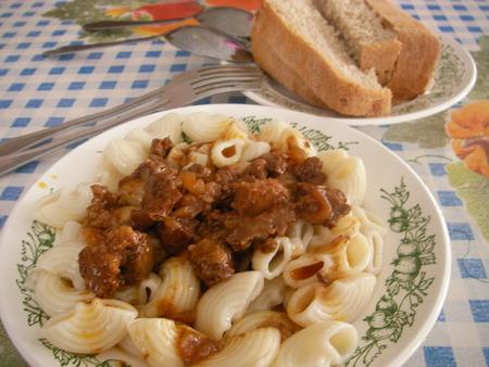 ambrosia: Il secondo goulash piatto e su un maccheroni guarnire - un pranzo di consueto nella sala da pranzo di lavoro Archivio Fotografico