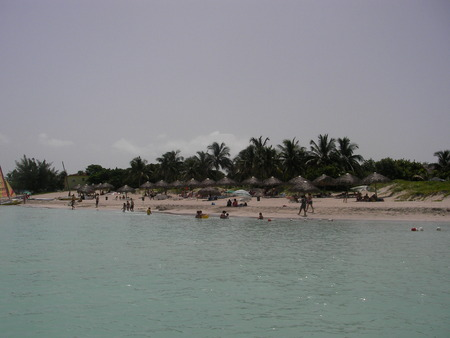 lodges: View of the Caribbean Sea with palm trees and lodges on the island Cuba Stock Photo