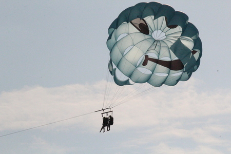 Highly the parachute soars up into the sky and soars in clouds attached by a cable to the boat