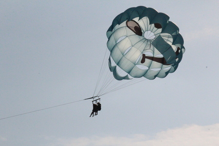 into: Highly the parachute soars up into the sky and soars in clouds attached by a cable to the boat
