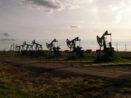 units: Long line of oil pumping units on a large-scale deposit of hydrocarbonic raw materials Stock Photo