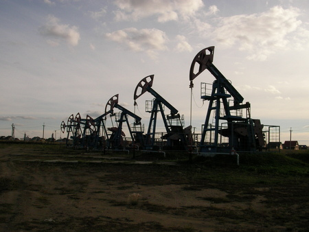 raw materials: Long line of oil pumping units on a large-scale deposit of hydrocarbonic raw materials Stock Photo
