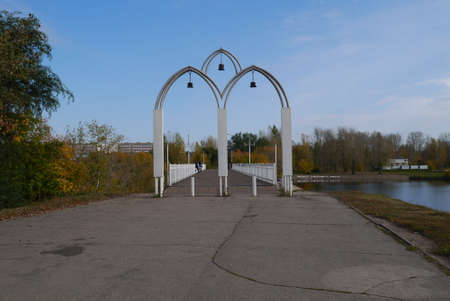 foot bridges: Arch entrance with bells on the foot bridge through the river Stock Photo