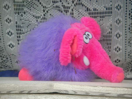waits: The soft toy - a multi-colored elephant waits when children with him play
