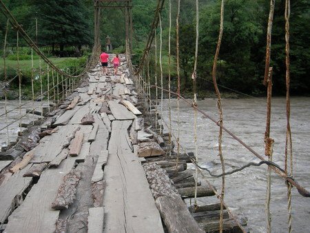 raging: Suspension bridge and suspended cable through the mountain raging river