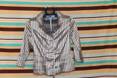 longitudinal: blouse in a longitudinal black-gray strip with accessories on a hanger Stock Photo