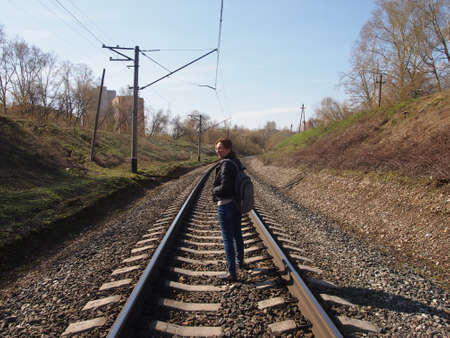 cross ties: Travel on railway cross ties in the clear spring afternoon with a backpack behind shoulders Railroad