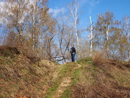 suburb: The woman walks in the spring on hills on the city suburb