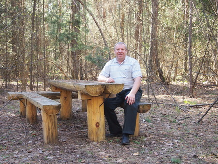 hammered: the man sits at the little table which is hammered together from logs Stock Photo