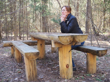 little table: the woman sits at the little table which is hammered together from logs