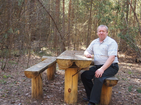 little table: the man sits at the little table which is hammered together from logs Stock Photo