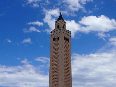 The minaret of the Muslim mosque towering highly in the sky Stock Photo