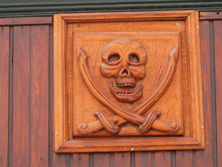 The head of the one-eyed pirate which is cut out on a wooden board