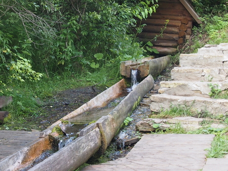 Spring water runs on a wooden trench