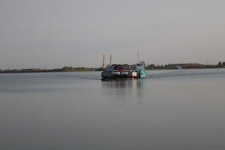 The ferry with cars slides on a water smooth surface of the lake