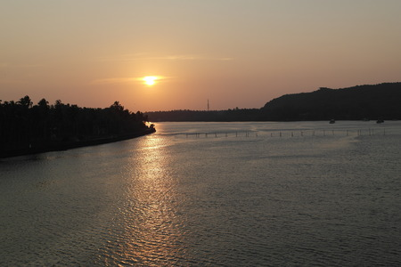 Sunset on the bank of the wide river in tropics