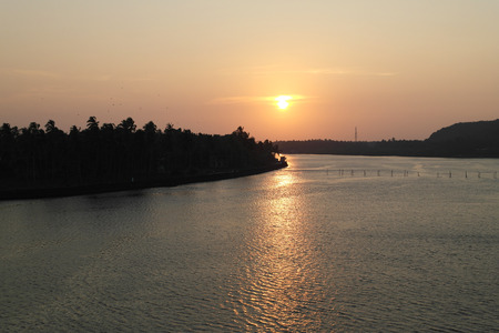 sunset over a plain surface of the river Stock Photo