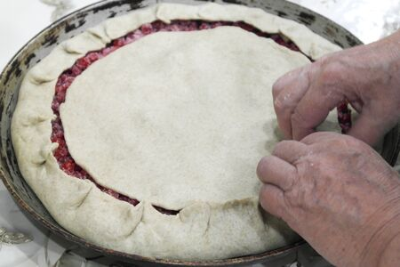 Grandmother pinches the edges of sweet pie