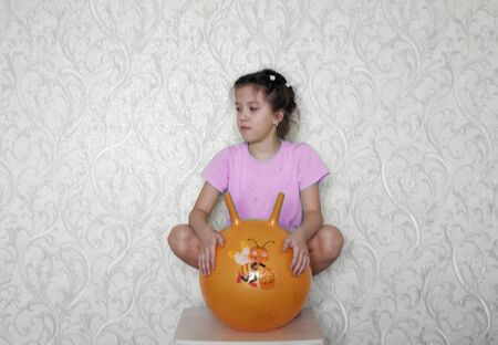 Pretty girl jumps on rubber sports ball with handles Standard-Bild
