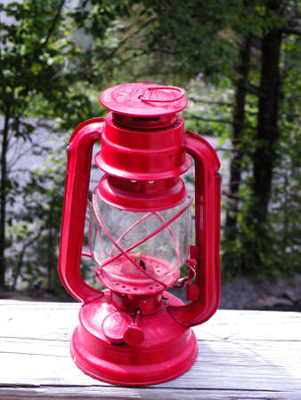 red oil lamp: camping lantern with woodsy background