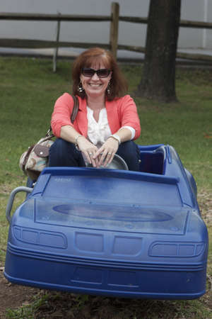 Middle age woman in toy car Imagens