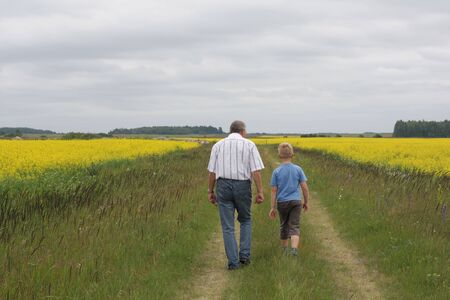 Grandson and grandfather between two fields of colza photo