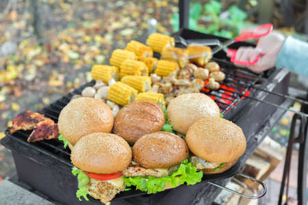 BBQ Burgers Breast With Vegetables On The Hot Charcoal Grill with hand on background