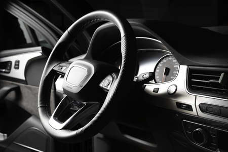 Black multifunctional leather steering wheel with gearshift paddles. In the cabin of a luxury SUV, dashboard, engine start button
