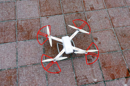 A quadrocopter drone stands in the snow on a red-brown tile. ready to fly in winter
