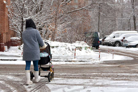 A woman with a stroller and a child goes into heavy snow. Walk with the baby in the pram. Badly cleaned streets of snow, the problem. Фото со стока