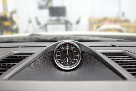 Chronometer with a clock in a luxury sports car. To measure lap times in races. Chronograph in top panel of premium car. Pitstop