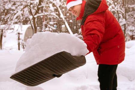 Full shovel of snow. man in red down jacket clears snow in backyard. Clears snowdrifts on path to home. In snowfall. Man remove snow with big plastic shovel with wooden handle