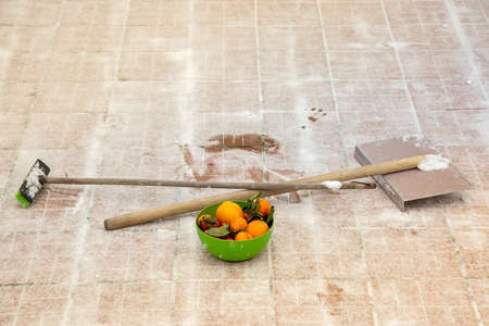 Mandarins and oranges in the green bowl. Vitamin Ð¡ to work well. Energy for working. Iron shovel and broom with wooden handle. lie on snow. like a cross on tile Standard-Bild