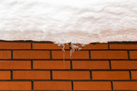 Red brick wall. texture. The gutter on the roof of the snow. icicles hanging from snowy roof. Danger hangs from the roof. Stock Photo