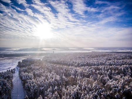 Aerial view on snow winter forest and field near road. Frozen river on background. Clouds with sun in blue sky 免版税图像