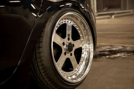 Alloy polished rims of a sports car. Wide wheels with stretched tires. Tuned low car