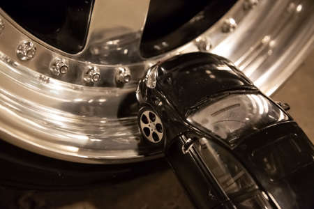 Black toy car stays on alloy rims of real car. Custom tuning wheels Stock Photo