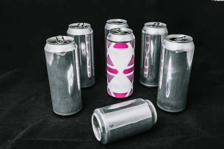 To be different. Stand out from the crowd. Beat the weak. Empty open cans, inequality concept. On a black background.