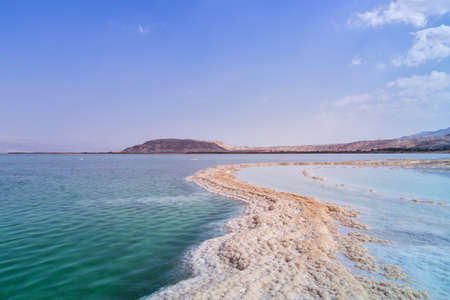 Israel. The salt flats of the Dead Sea. Blue sky and mountains in the background.  The path from salt picturesquely curls in salty water.