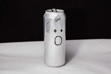 Concept of beaten man. Astonished emoticon on aluminium can, Emoji with surprised face. On black background Imagens