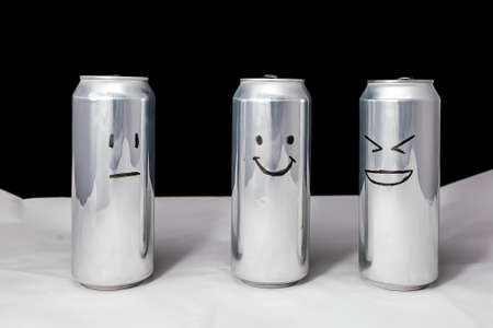 Concept of ridicule. Joke over a friend but its not funny to him. Aluminium cans with drowing emoticons. Emoji of laugh, smile and no emotions.