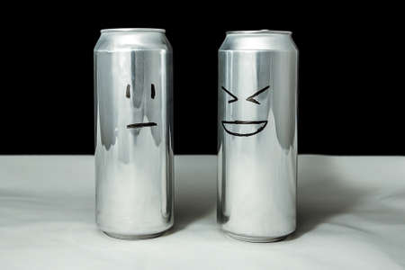 Concept of friends. Joke over a friend but its not funny. Aluminium cans with drowing emoticons, Emoji of laugh and poker face