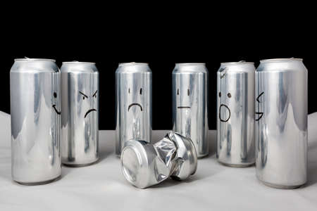 One little beaten surrounded by big. Concept of empty people with different emotions. Aluminium cans with drawned emoji on black background Imagens