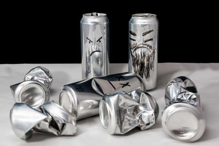 Concept of terrorism. Aluminium cans with drawn emoji. Crumpled open and empty. Angry emoticons on black background