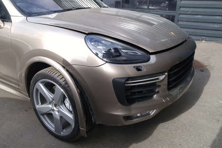 Moscow. February 2019. Accident Porsche Cayenne Turbo in gold color. Broken front grill, rear bumper, wheel fenders and wheels.