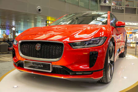 Singapore. March 2019. Orange Jaguar I-Pace all electric SUV. Front view. Standed in airport. Cars of the future