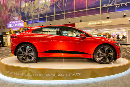 Singapore. March 2019. Orange Jaguar I-Pace all electric SUV. Side view. I pace in Changhi airport on the stand.