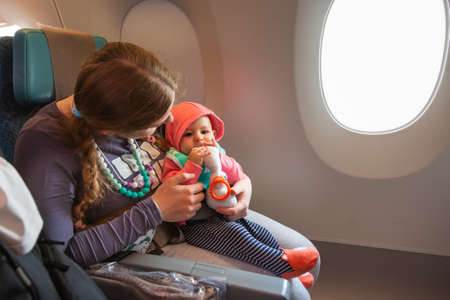 Mother carry her infant baby during flight. Sitting together near the window in airplane 版權商用圖片