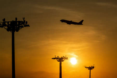 Passenger plane is takeoff during a beautiful sunrise. Lamp tower of spotlights on the pillars at the airport.