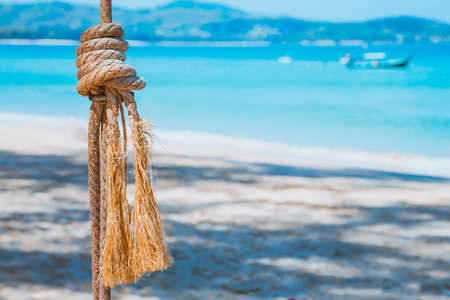 A rope with a knotted sea knot against a blue sea and sandy beach. Summer leisure at the water. Closeup Banque d'images